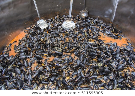 mussels in red sauce in big cauldron on a street market stock photo © smuki