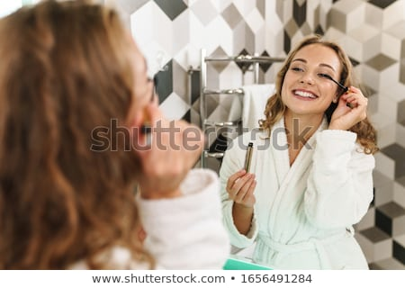 cheerful woman standing and doing makeup in bathroom stock photo © deandrobot