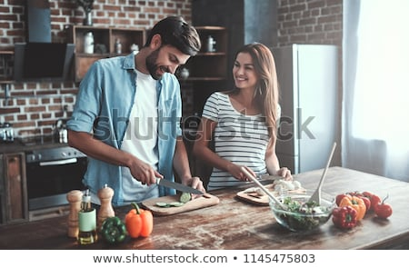 young man and woman cooking salad together at kitchen stock photo © dashapetrenko