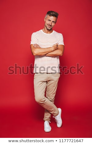 Full length photo of unshaved man in striped t-shirt smiling and Stock photo © deandrobot