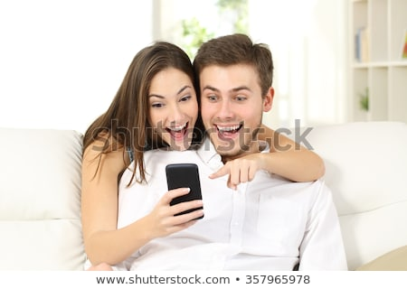 Portrait of a surprised young couple sitting together Stock photo © deandrobot
