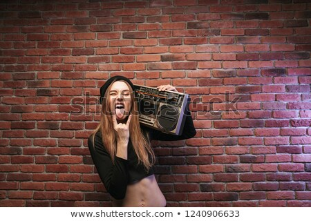 Image of cool hip hop woman 20s, standing against brick wall and Stock photo © deandrobot
