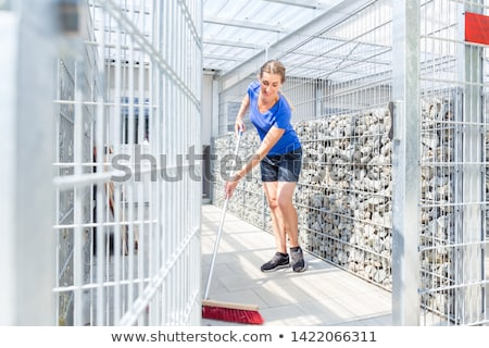 Zookeeper woman working on cleaning cage in animal shelter Stock photo © Kzenon