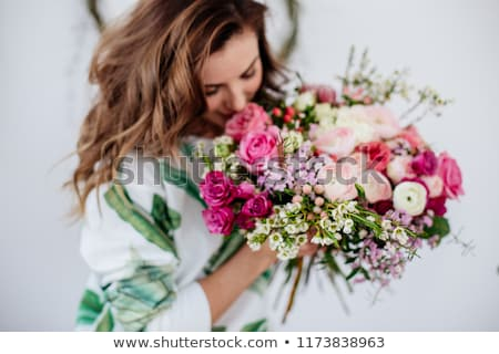 florist woman is wrapping fresh rose bouquet in a decorative paper on a wooden table on a light wall stock photo © artjazz