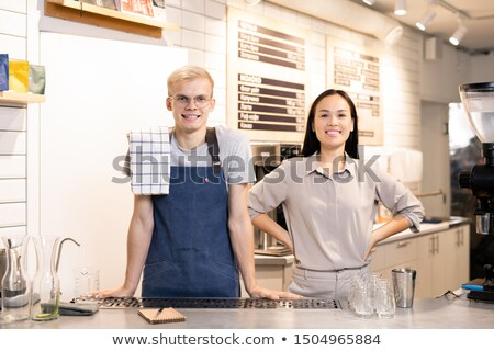 Two young successful workers of contemporary cafe or restaurant in uniform Stock photo © pressmaster