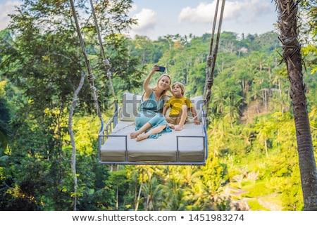 Young boy swinging in the jungle rainforest of Bali island, Indonesia. Swing in the tropics. Swings  Stock photo © galitskaya