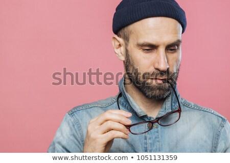 Headshot of pensive bearded man looks thoughtfully down, holds glasses, wears denim jacket and hat,  Stock photo © vkstudio