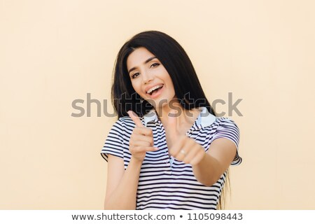 Shot of attractive European female gives double thumb up, has positive expression, has white teeth w Stock photo © vkstudio