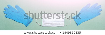 Doctor wearing blue face medical mask and green latex gloves holding tablet pill on grey hospital wa Stock photo © DenisMArt