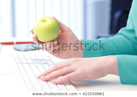 Woman working on her laptop and holding an apple stock photo © photography33