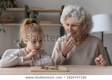 Little girl playing chess with grandmother Stock photo © photography33