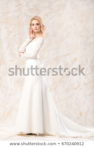 Elegant young woman in white long dress posing indoors Stock photo © amok