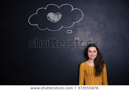 Woman thinking about love and standing with blackboard behind her Stock photo © deandrobot
