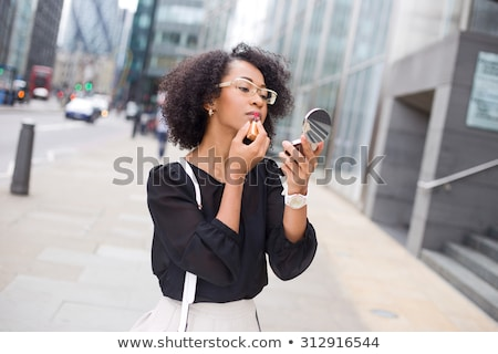 young woman applying lipstick on city street stock photo © elenaphoto