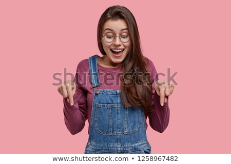 Cheerful lady posing over dark background pointing to camera. Stock photo © deandrobot