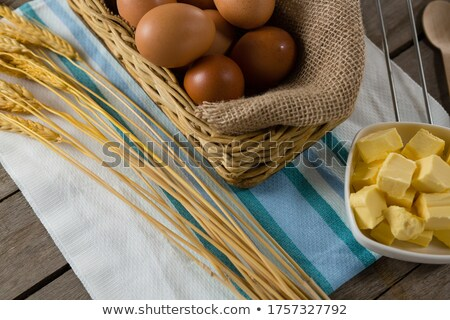 Eggs in wicker basket with wheat, cheese, and flour on wooden table Stock photo © wavebreak_media