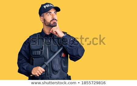Young serious hispanic policeman with baton. Stock photo © RAStudio