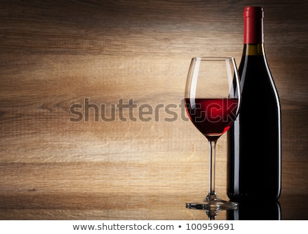 Glass of red wine with bottle with shape on black Stock photo © DenisMArt