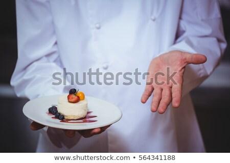 proud chef holding a plate of cheesecake desert stock photo © wavebreak_media