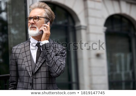 Senior om de afaceri mobil palmier în picioare în aer liber Imagine de stoc © IS2