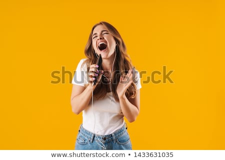 Image of pleased woman wearing earphones rejoicing and holding c Stock photo © deandrobot