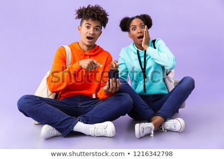 African american man and woman wearing backpacks using cell phon Stock photo © deandrobot