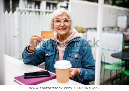 senior woman with bill for coffee at street cafe stock photo © dolgachov
