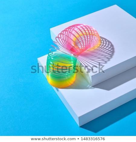 Toy plastic rainbow slinky with shadows on blue. Stock photo © artjazz