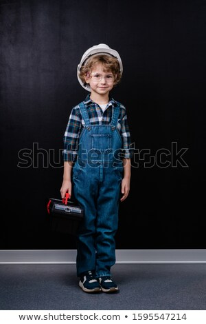 Adorable little boy in hardhat, denim overalls and eyeglasses holding toolbox Stock photo © pressmaster