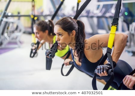 Young determined fitness woman doing exercises at chest press ma Stock photo © boggy