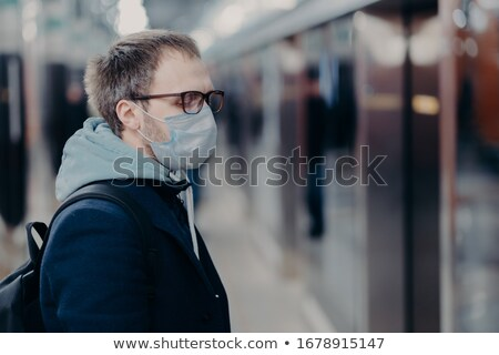 Health care and illness concept. Profile shot of European man wears medical mask, poses on station i Stock photo © vkstudio