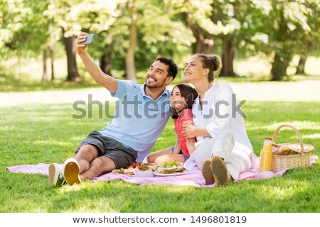 family with smartphone having picnic at park Stock photo © dolgachov