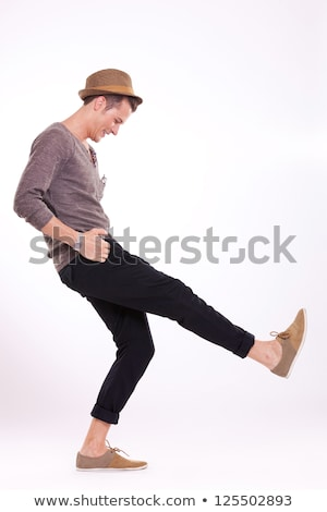 casual man with hand on hat and in pocket stock photo © feedough