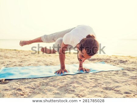 man doing handstand on beach Stock photo © PetrMalyshev