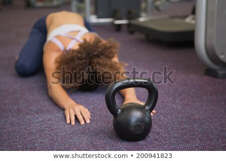 Fit woman lying in childs pose with kettlebell Stock photo © wavebreak_media