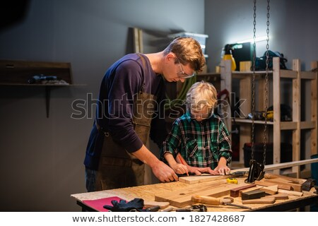 happy little boy with plank and ruler at workshop Stock photo © dolgachov