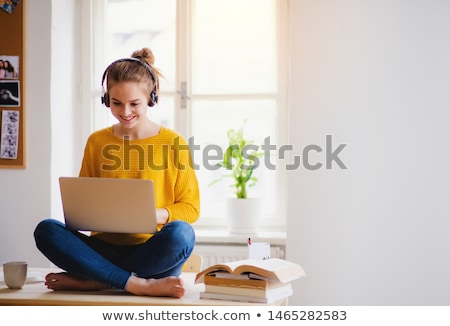 a young girl is sitting at a computer desk holding a yellow marker in her hand and talking on the p stock photo © traimak