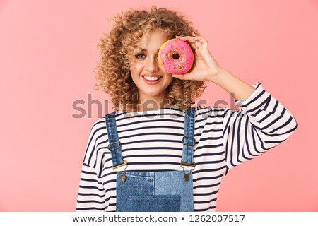 Image of positive curly woman 20s wearing casual clothes eating  Stock photo © deandrobot
