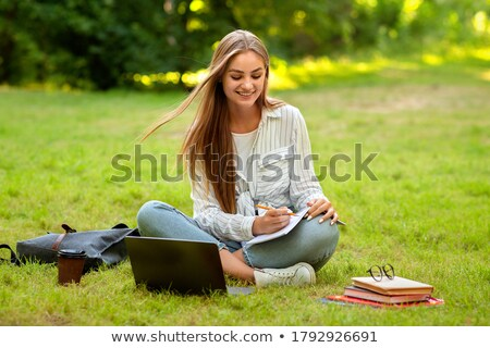 Beautiful woman sitting outdoors using laptop computer listening music with earphones. Stock photo © deandrobot