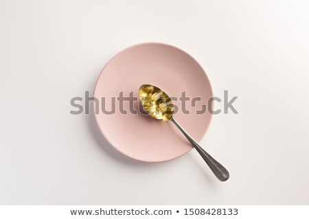 Vitamin pills on a white plate in a shape of fish with spoon and fork in a girl's hands on a blue ba Stock photo © artjazz