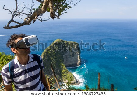Young man with VR glasses at Kelingking beach on the island of N Stock photo © boggy