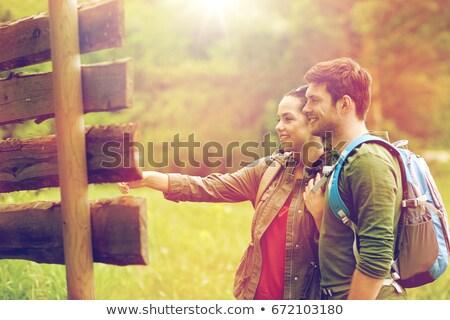 ストックフォト: Couple Of Travelers With Backpacks At Signpost