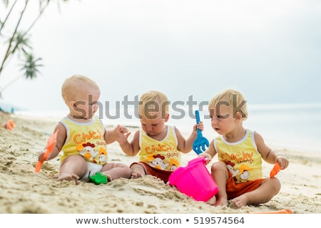 Three baby Toddler sitting on a tropical beach in Thailand and playing with sand toys. The yellow sh Stock photo © galitskaya