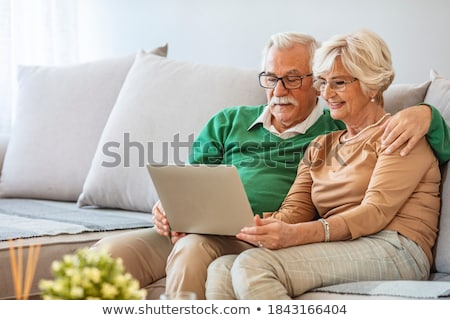Side view of active senior couple having fun while relaxing on sun lounger at beach Stock photo © wavebreak_media