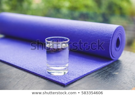 Yoga mat, water, orange and mango on a wooden background. Equipment for yoga. Concept healthy lifest Stock photo © galitskaya
