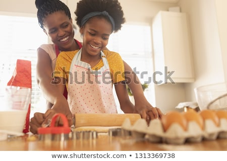 Low angle view of happy African American mother and daughter baking cookies in kitchen at home Stock photo © wavebreak_media