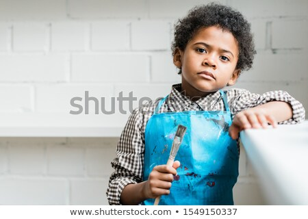 serious african schoolboy in blue apron holding paintbrush in hand stock photo © pressmaster
