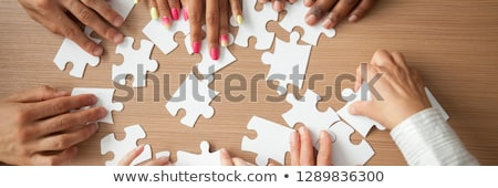 Man's Hand Solving Jigsaw Puzzle Stock photo © AndreyPopov
