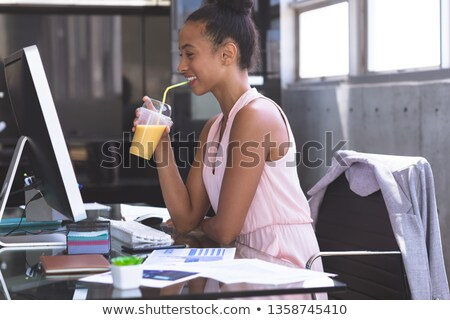 Side view of happy mixed-race businesswoman having milkshake while working on computer at desk in th Stock photo © wavebreak_media