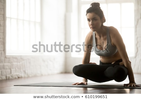 Woman doing  Ashtanga Vinyasa Yoga  arm balance asana Tolasana Stock photo © dmitry_rukhlenko